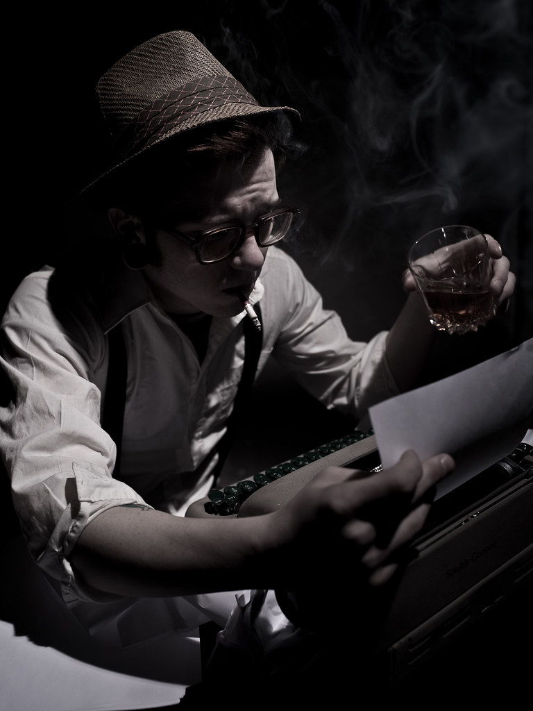 Photo of a stereotypical author. Youngish with a hat on holding a whisky in front of an old fashioned typewriter.